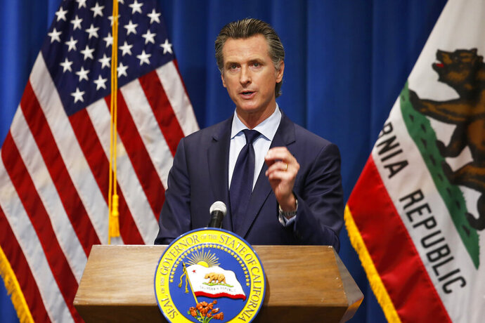 FILE - In this Thursday, May 14, 2020, file photo California Gov. Gavin Newsom discusses his revised 2020-2021 state budget during a news conference in Sacramento, Calif. Gov. Newsom signed a $202.1 billion state budget Monday, June 29, in Sacramento, Calif. The budget closes an estimated $54.3 billion deficit through a combination of spending cuts, internal borrowing and temporary tax increases on businesses. Like most states, California's deficit was driven by the economic downturn caused by the coronavirus. (AP Photo/Rich Pedroncelli, Pool, File)