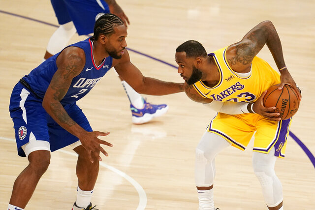 Los Angeles Lakers forward LeBron James, right, is defended by Los Angeles Clippers forward Kawhi Leonard during the first half of an NBA basketball game Tuesday, Dec. 22, 2020, in Los Angeles. (AP Photo/Marcio Jose Sanchez)