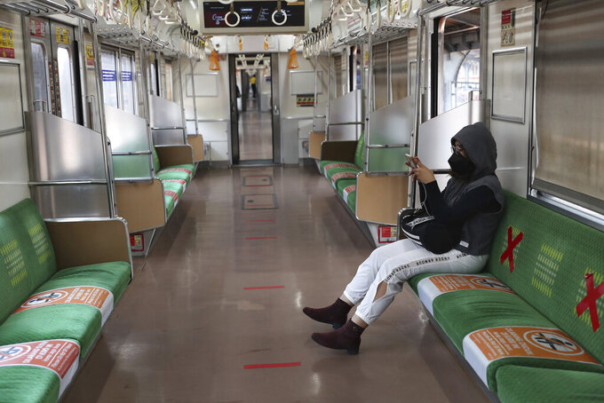 A woman wearing a face mask to curb the spread of coronavirus sits inside an empty train at the Jakarta Kota train station in Jakarta, Indonesia, Wednesday, July 28. (AP Photo/Tatan Syuflana)