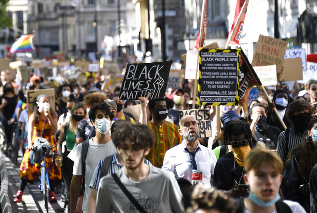 People, most wearing protective masks against the spread of coronavirus, march to Britain's Parliament in central London, Saturday, June 20, 2020, during a protest organised by Black Lives Matter, in the wake of the killing of George Floyd by police officers in Minneapolis, USA last month that has led to anti-racism protests in many countries calling for an end to racial injustice. Anti-racism demonstrators are holding a fourth weekend of protests across the U.K. (AP Photo/Alberto Pezzali)