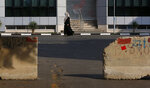 A Palestinian woman walks on a road next to barriers during a lockdown imposed following the discovery of a rise in coronavirus cases in Gaza City, Monday, Aug. 31, 2020. (AP Photo/Hatem Moussa)