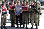 FILE - In this Aug. 1, 2017 file photo, paramilitary police and members of the special forces escort former Air Force commander Akin Ozturk and other suspects of a failed coup in 2016, outside the courthouse at the start of a trial, in Ankara, Turkey. Turkey's state-run news agency says Thursday, June 20, 2019, a court in Ankara has sentenced several people, including Ozturk, accused of being the ringleaders of the 2016 failed military coup, to life terms in prison. (AP Photo/Burhan Ozbilici, File)
