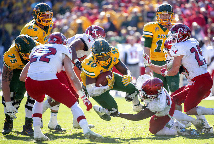 North Dakota State running back Lance Dunn (10) is tripped up by Eastern Washington linebacker Chris Ojoh (58) during the second half of the FCS championship NCAA college football game, Saturday, Jan. 5, 2019, in Frisco, Texas. North Dakota State won 38-24. (AP Photo/Jeffrey McWhorter)