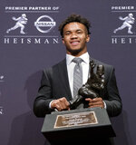 FILE - In this Dec. 8, 2018, file photo, Oklahoma quarterback Kyler Murray poses with the Heisman Trophy after winning the award in New York. Kyler Murray, the first-round Major League Baseball draft pick and Heisman Trophy-winning Oklahoma quarterback, says he is declaring himself eligible for the NFL draft. Murray announced his decision Monday, Jan. 14, 2019, in a tweet. (AP Photo/Craig Ruttle, File)