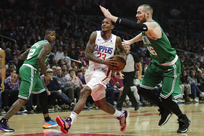 Los Angeles Clippers' Lou Williams, center, drives to the basket under pressure by Boston Celtics' Aron Baynes during the first half of an NBA basketball game, Monday, March 11, 2019, in Los Angeles. (AP Photo/Jae C. Hong)