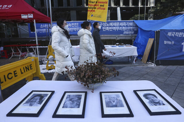 Portraits of late former South Korean comfort women are displayed near the Japanese Embassy in Seoul, South Korea, Friday, Jan. 8, 2021. A South Korean court on Friday ordered Japan to financially compensate 12 South Korean women forced to work as sex slaves for Japanese troops during World War II, the first such ruling expected to rekindle animosities between the Asian neighbors. (AP Photo/Ahn Young-joon)