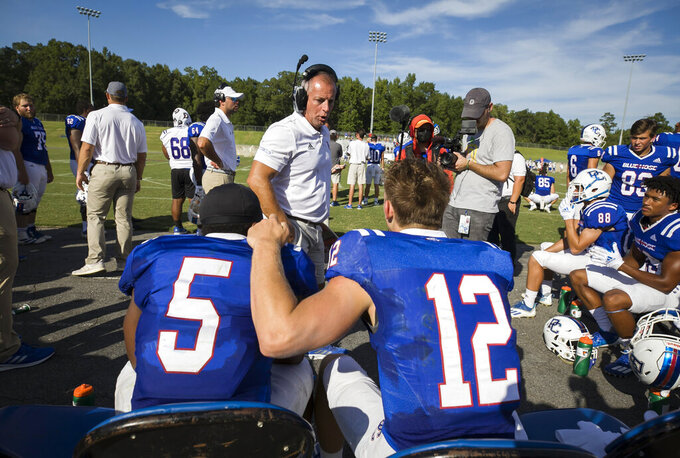 Presbyterian head coach Kevin Kelley speaks with running back Delvecchio Powell II (5) and quarterback Ren Hefley (12) on the sideline against St. Andrews during a college football game, Saturday, Sept. 4, 2021, at Bailey Memorial Stadium in Clinton, S.C. (Sam Wolfe/The State via AP)