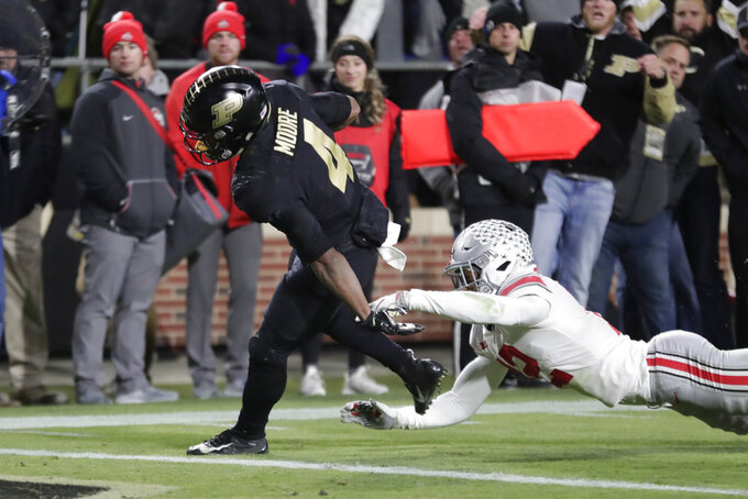 Purdue wide receiver Rondale Moore (4) scores a touchdown after breaking the tackle of Ohio State safety Isaiah Pryor (12) during the first half of an NCAA college football game in West Lafayette, Ind., Saturday, Oct. 20, 2018. (AP Photo/Michael Conroy)