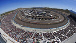 FILE - In this March 13, 2016, file photo, the crowd watches drivers through the first two turns during a NASCAR Sprint Cup Series auto race at Phoenix International Raceway, in Avondale, Ariz. NASCAR made the first significant changes to its schedule in years by shuffling the 2020 season into a freshened new sequence that tries to meet the wants of fans to the best of NASCAR's current ability. (AP Photo/Ross D. Franklin, File)