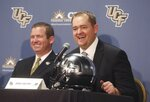 FILE - In this Dec. 5, 2017, file photo, Josh Heupel, right, is introduced as the new Central Florida head football coach by Danny White, UCF Athletic director, in Orlando, Fla. Josh Heupel has either the most difficult job of any head coach in the country taking over a new team this season or the easiest. (Red Huber/Orlando Sentinel via AP, File)