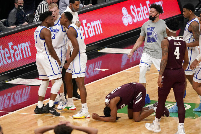 Missouri State's Demarcus Sharp (0) reacts as Drake's Joseph Yesufu (1), Garrett Sturtz (3) and D.J. Wilkins celebrate following an NCAA college basketball game in the semifinal round of the Missouri Valley Conference men's tournament Saturday, March 6, 2021, in St. Louis. Drake won 71-69. (AP Photo/Jeff Roberson)