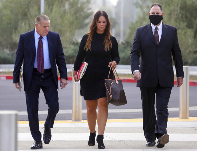 Attorneys Mike Rains, left, Julia Fox, center, and San Leandro Police Officer Jason Fletcher, right, arrive at the East County Hall of Justice on Tuesday, Sept. 15, 2020, in Dublin, Calif. A police officer facing manslaughter charges in the shooting death of a Black man inside a San Francisco Bay Area Walmart store was handcuffed and taken to jail following a court appearance Tuesday. Judge Barbara Dickinson denied a defense attorney request to allow San Leandro Police Officer Jason Fletcher to immediately post $200,000 bail, saying it was not the court's practice to allow that. (Aric Crabb/Bay Area News Group via AP)