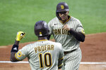 San Diego Padres Jurickson Profar, left, greets Trent Grisham, right, after Grisham's home run in the fourth inning during a baseball game on Sunday, April 11, 2021, in Arlington, Texas. (AP Photo/Richard W. Rodriguez)