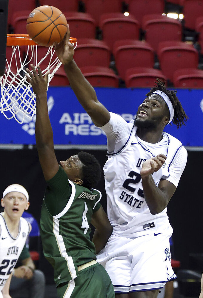 Utah State center Neemias Queta (23) blocks a shot from Colorado State guard Isaiah Stevens (4) during the second half of an NCAA college basketball game in the semifinal round of the Mountain West Conference men's tournament Friday, March 12, 2021, in Las Vegas. (AP Photo/Isaac Brekken)