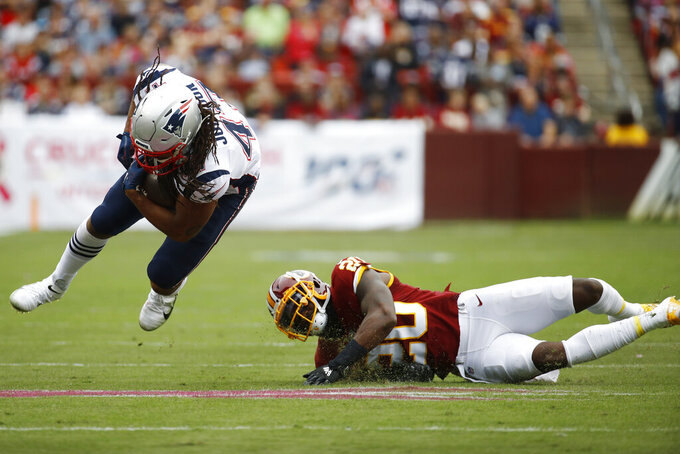 New England Patriots fullback Jakob Johnson (47)- is tripped up by Washington Redskins strong safety Landon Collins (20) during the first half of an NFL football game, Sunday, Oct. 6, 2019, in Landover, Md. (AP Photo/Patrick Semansky)