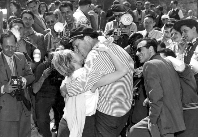 In this April 28, 1955 file photo actor and singer Eddie Constantine kisses his new wife Helene Mussel for the photographers surrounding during the International Film festival in Cannes, France. It is one of the indelible moments the Cannes Film Festival has created throughout its history, and more were likely to be made when it opened on Tuesday, May 12, 2020. This year's festival has been postponed due to the coronavirus pandemic. (AP Photo/Babout, File)