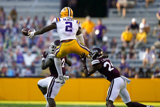LSU tight end Arik Gilbert (2) tries to pull in a pass against Mississippi State safety Dylan Lawrence (24) and safety Tyrus Wheat in the second half an NCAA college football game in Baton Rouge, La., Saturday, Sept. 26, 2020. Mississippi State won 44-34. (AP Photo/Gerald Herbert)