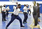 Baltimore city police trainee Alhaji Fofana, of Philadelphia, uses a baton during defense tactic training, Wednesday, Aug. 4, 2021, in Baltimore. Baltimore's police force is struggling to meet staffing targets to fully comply with a reform intervention and get out from under federal oversight. The agency has some 400 vacancies among its sworn staff and its recruitment efforts just can't keep pace with those leaving their jobs.(AP Photo/Steve Ruark)