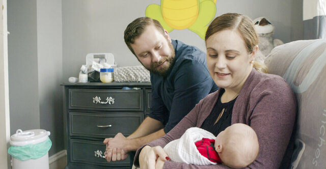 In this undated photograph provided by Penn Medicine, Jennifer and Drew Gobrecht look at their baby, Benjamin, at home in Ridley Park, Pa. Jennifer gave birth in November 2019 following a uterine transplant. (Penn Medicine via AP)