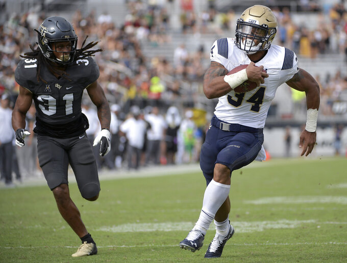 File-This Nov. 10, 2018, file photo shows Navy fullback Mike Martin (34) rushing for a 14-yard touchdown in front of Central Florida defensive back Aaron Robinson (31) during the second half of an NCAA college football game in Orlando, Fla. Although Navy is having a down year, it snapped a seven-game skid with a 37-29 win over Tulsa in which senior quarterback Zach Abey rushed for 128 yards and two touchdowns on 26 carries. Navy amassed 389 yards on the ground in the game. (AP Photo/Phelan M. Ebenhack, File)