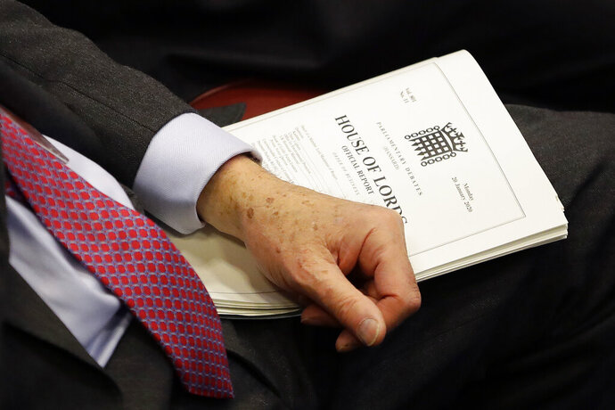 A member holds a document inside the House of Lords as the European Withdrawal Agreement Bill is debated in London, Tuesday, Jan. 21, 2020. Britain's House of Lords is considering the European Withdrawal Agreement Bill, which is due to pass through its final stages before returning to the House of Commons. (AP Photo/Kirsty Wigglesworth, pool)