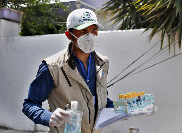 A health worker leaves after collecting samples from a family for coronavirus testing at a neighborhood in Islamabad, Pakistan, Monday, June 8, 2020. The number of new coronavirus infections in Pakistan continued to spiral upward, as the nation of 220 million people surpassed 100,000 cases as of Sunday with more than 2,000 deaths. (AP Photo/Anjum Naveed)