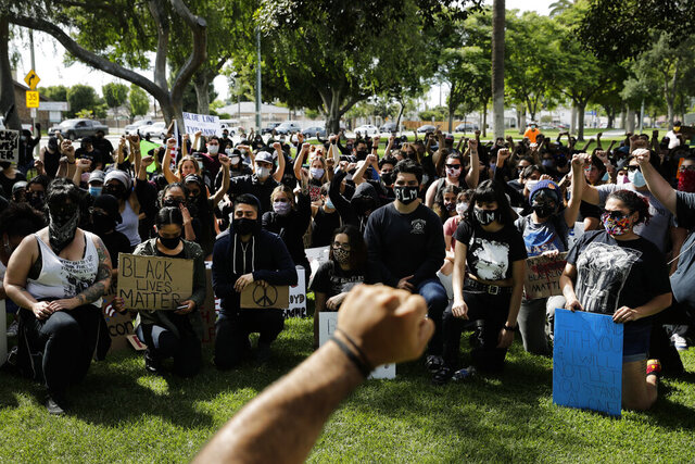 Demonstrators raise their fists Monday, June 1, 2020, during a protest over the death of George Floyd in Anaheim, Calif. (AP Photo/Jae C. Hong)