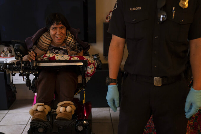 Barbara Franco, who has muscular dystrophy, smiles while talking to Torrance firefighters after receiving the second dose of the Pfizer COVID-19 vaccine at her apartment, Wednesday, May 12, 2021, in Torrance, Calif. Teamed up with the Torrance Fire Department, Torrance Memorial Medical Center started inoculating people at home in March, identifying people through a city hotline, county health department, senior centers and doctor's offices, said Mei Tsai, the pharmacist who coordinates the program. (AP Photo/Jae C. Hong)