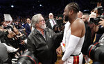 Miami Heat owner Mickey Arison talks to Heat guard Dwyane Wade after the final NBA basketball game of Wade's NBA career, against the Brooklyn Nets on Wednesday, April 10, 2019, in New York. (AP Photo/Kathy Willens)