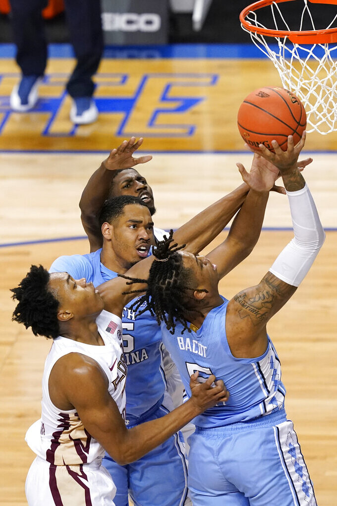 North Carolina forward Armando Bacot (5) goes up for a shot with the help of teammate forward Garrison Brooks, middle, as Florida State guard Scottie Barnes, left, and Florida State guard Sardaar Calhoun, top, defend during the second half of an NCAA college basketball game in the semifinal round of the Atlantic Coast Conference tournament in Greensboro, N.C., Friday, March 12, 2021. (AP Photo/Gerry Broome)