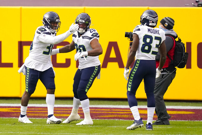 Seattle Seahawks running back Carlos Hyde (30), left, celebrating his touchdown against the Washington Football Team with teammates running back Rashaad Penny (20) and wide receiver David Moore (83) during the second half of an NFL football game, Sunday, Dec. 20, 2020, in Landover, Md. (AP Photo/Andrew Harnik)