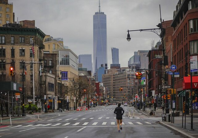 A lone jogger run on a partially empty 7th Avenue, resulting from citywide restrictions calling for people to stay indoors and maintain social distancing in an effort to curb the spread of COVID-19, Saturday March 28, 2020, in New York. President Donald Trump says he's considering a quarantine affecting residents of the state and neighboring New Jersey and Connecticut amid the coronavirus outbreak, but New York Gov. Andrew Cuomo said that roping off states would amount to