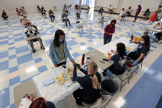 Acushnet Fire EMT's administer a COVID-19 antibodies test to a teacher, as the rest of the Ford Middle School staff in Acushnet, Mass., wait to be tested while sitting in appropriate social distanced desks in the schools gym on Wednesday, Sept. 16, 2020. School starts Thursday. (Peter Pereira/The Standard-Times via AP)