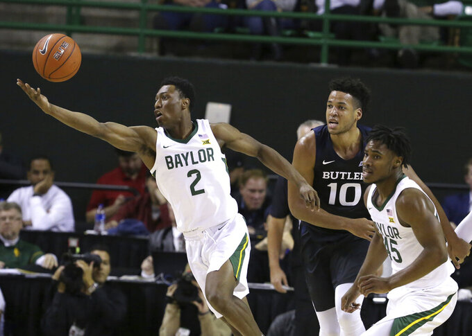 Baylor guard Devonte Bandoo, left, reaches for a loose rebound past Butler forward Bryce Nze, center, and guard Davion Mitchell, right, in the first half of an NCAA college basketball game, Tuesday, Dec. 10, 2019, in Waco, Texas. (AP Photo/Rod Aydelotte)