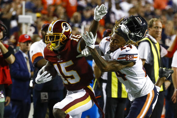 Washington Redskins wide receiver Steven Sims (15) stiff arm's the helmet off of Chicago Bears cornerback Buster Skrine (24) during the second half of an NFL football game Monday, Sept. 23, 2019, in Landover, Md. (AP Photo/Patrick Semansky)