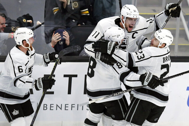 Los Angeles Kings center Anze Kopitar (11) is congratulated by teammates after his game-winning goal off Boston Bruins goaltender Tuukka Rask during an overtime period of an NHL hockey game in Boston, Tuesday, Dec. 17, 2019. The Kings won 4-3. (AP Photo/Charles Krupa)