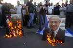 Palestinians burn pictures of U.S. President Donald Trump, left, and Israeli Prime Minister Benjamin Netanyahu during a protest against Trump's mideast initiative, in the West Bank city of Nablus, Saturday, May 30, 2020.(AP Photo/Majdi Mohammed)