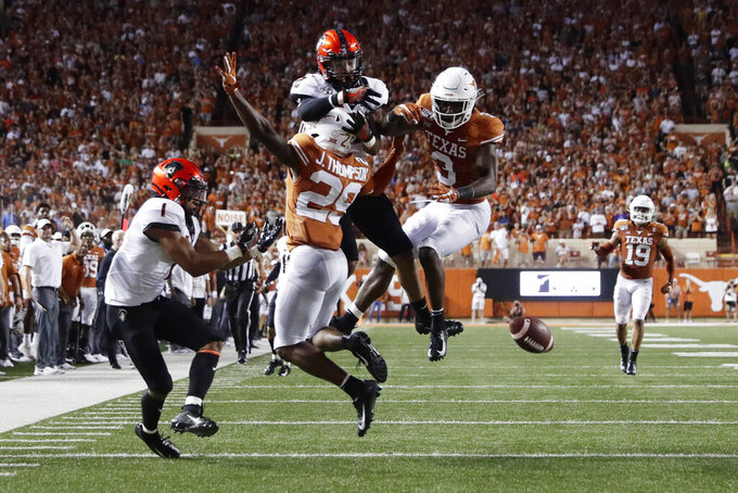 Texas defensive back Josh Thompson (29) and defensive back Jalen Green (3) break up a pass intended for Oklahoma State wide receiver Tylan Wallace (2) during the first half of an NCAA college football game Saturday, Sept. 21, 2019, in Austin, Texas. (AP Photo/Eric Gay)