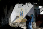 A man walks past an image of the Virgin of Guadalupe mural with text that reads in Spanish