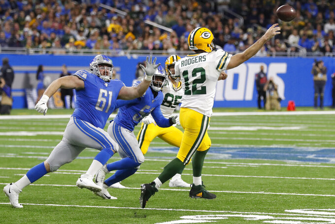 FILE - Green Bay Packers quarterback Aaron Rodgers (12) throws as Detroit Lions defensive tackle Jamie Meder (61) applies pressure during the second half of an NFL football game, Sunday, Dec. 29, 2019, in Detroit. Aaron Rodgers will begin his 16th season with Green Bay looking  to continue his remarkable run of success against NFC North opponents as the Packers visit Minnesota. The Packers own a 47-18-1 record in games Rodgers has played against NFC North foes, including a 6-0 mark last season. (AP Photo/Carlos Osorio, File)