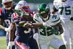 New York Jets' Michael Carter, right, runs the ball during the second half of an NFL football game against the New England Patriots, Sunday, Sept. 19, 2021, in East Rutherford, N.J. (AP Photo/Frank Franklin II)