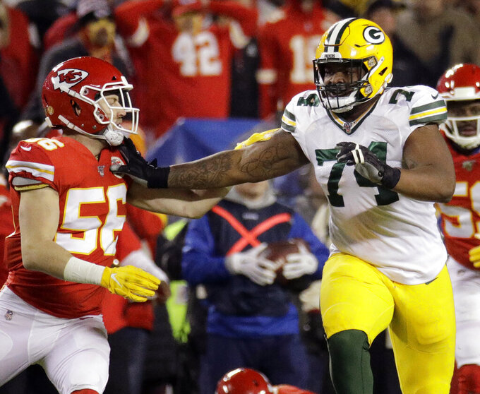 FILE - In this Oct. 27, 2019, file photo, Green Bay Packers offensive guard Elgton Jenkins (74) blocks Kansas City Chiefs linebacker Ben Niemann (56) during the first half of an NFL football game in Kansas City, Mo. Jenkins has played every position on the offensive line but right guard this season. (AP Photo/Charlie Riedel, File)