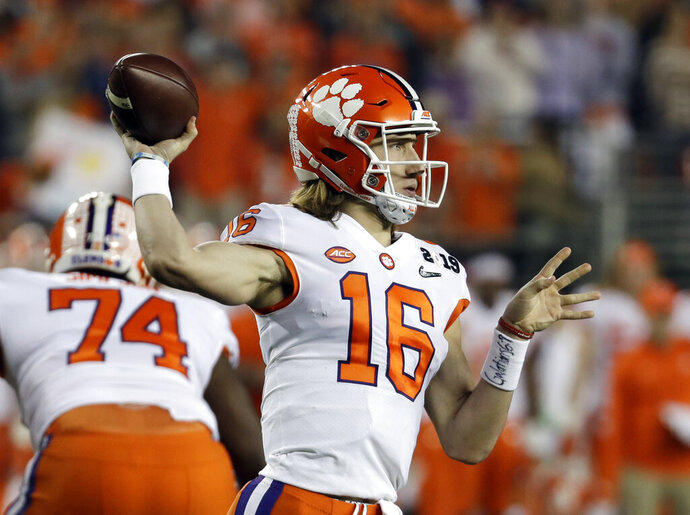 """FILE - In this Jan. 7, 2019, file photo, Clemson's Trevor Lawrence throws during the first half the NCAA college football playoff championship game against Alabama, in Santa Clara, Calif. Sure, Clemson lost all four of its """"Power Rangers"""" defensive line and seven starters on defense from its title team. But the Tigers' offense, led by Heisman Trophy candidates quarterback Trevor Lawrence and tailback Travis Etienne, looks ready to operate at an even higher level than a year ago when it averaged 527 yards and 44.3 points a game.  (AP Photo/Chris Carlson, File)"""