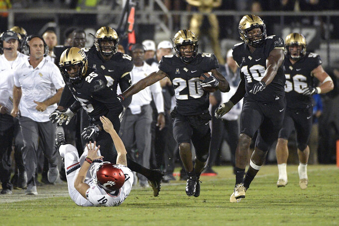Central Florida defensive back Brandon Moore (20) returns a blocked punt 60-yards as defensive lineman Titus Davis (10) helps and defensive back Kyle Gibson (25) blocks Cincinnati place kicker Cole Smith (19) during the first half of an NCAA college football game Saturday, Nov. 17, 2018, in Orlando, Fla. (AP Photo/Phelan M. Ebenhack)