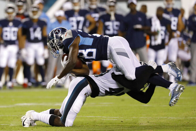 Tennessee Titans' Dalyn Dawkins, top, is tackled by Philadelphia Eagles' Josh Hawkins during the second half of a preseason NFL football game Thursday, Aug. 8, 2019, in Philadelphia. (AP Photo/Michael Perez)