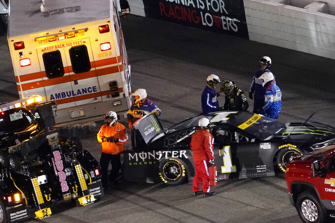 Kurt Busch (1) is helped out of his car after a spinout during the NASCAR Cup series auto race in Richmond, Va., Saturday, Sept. 11, 2021. (AP Photo/Steve Helber)