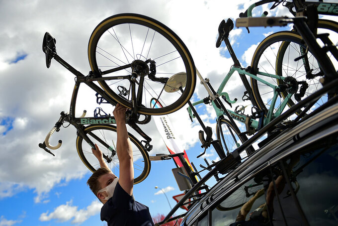 A Jumbo staff member holds up the bicycle of Primoz Roglic before the second stage of La Vuelta between Pamplona and Lekunberri, in Pamplona, northern Spain, Wednesday, Oct. 21, 2020. (AP Photo/Alvaro Barrientos)