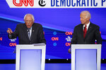 Democratic presidential candidate Sen. Bernie Sanders, I-Vt., left, speaks as former Vice President Joe Biden listens during a Democratic presidential primary debate hosted by CNN/New York Times at Otterbein University, Tuesday, Oct. 15, 2019, in Westerville, Ohio. (AP Photo/John Minchillo)