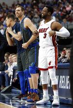 Dallas Mavericks forward Dirk Nowitzki, left, and Miami Heat guard Dwyane Wade, right, prepare to enter during the first half of an NBA basketball game in Dallas, Wednesday, Feb. 13, 2019. (AP Photo/Tony Gutierrez)