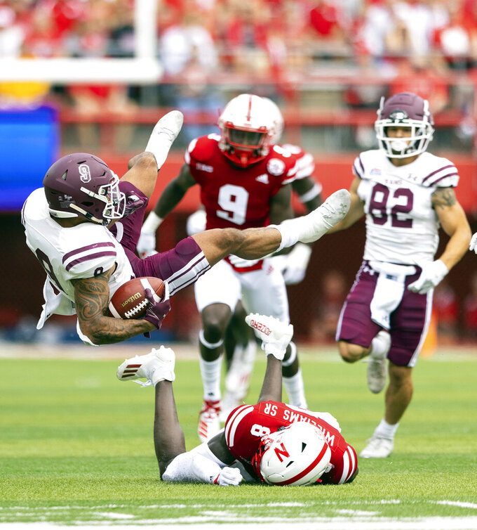 Fordham's Zach Davis (9) goes airborne after being tripped up by Nebraska's Deontai Williams Sr. (8) during the first half of an NCAA college football game Saturday, Sept. 4, 2021, at Memorial Stadium in Lincoln, Neb. (AP Photo/Rebecca S. Gratz)
